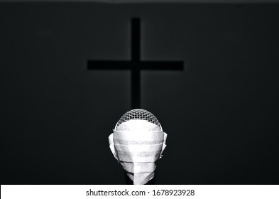 Lone microphone with mask in front of the cross