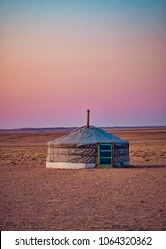 Lone Mongolian Yurt in Gobi Desert at Dusk with Evening Sun Light and Pink Sky. Yurt in dry plain.
