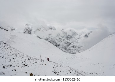 A lone monk on the snow-covered Thorong La pass on a cloudy day, Nepal.