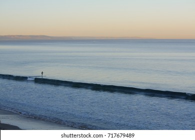 A lone paddle boarder slices through the ocean stillness at dawn, near Adelaide, Moana Beach, South Australia