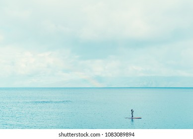 A Lone Paddleboarder Enjoys Some Morning Tranquility In Napili Bay On The Island Of Maui With Molokai In The Background