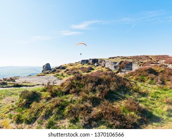 A lone paraglider flys low over Curbar Edge on a hazy spring day.
