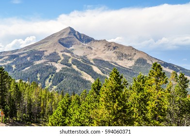 Lone Peak rises above the pine tree forest in Montana.