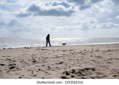 Lone person and dog walk along the sands of Skegness beach on the east coast of England in the county of Lincolnshire on a summers day.