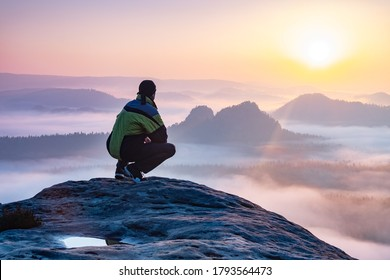 Ein einziger Sitzer blickt auf einen Berg, der von Nebel und Wolken umhüllt ist und den Gipfel sichtbar macht. Scenic Landschaftsfoto-Composite.