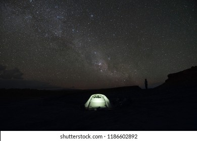 A lone person star gazes at the milky way in front of a tent at night in Argentina