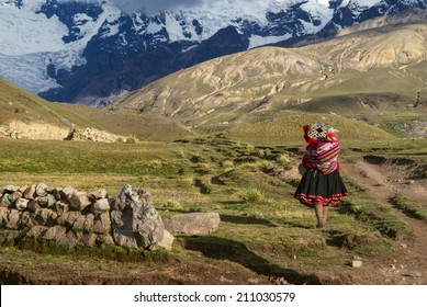 Lone peruvian woman walking with child on her back in south american Andes
