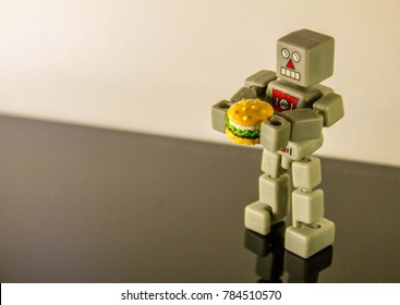 A lone robot holding a beef burger.