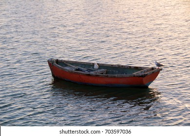 A lone rowing boat sits anchored or moored in a harbor, port or marina.