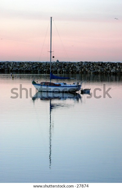 a lone sail boat sits in the water with its mirror reflection durring sunrise