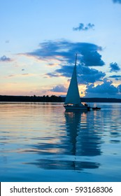 A lone sail boat at sunset, colorful sky