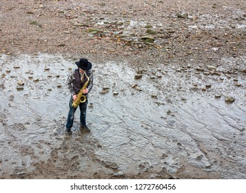 Lone saxophonist wearing a check shirt and black hat busks on a pebble river bed as the audience look down. The brass instrument shines brightly in contrast to the muddy grey tones of the shore