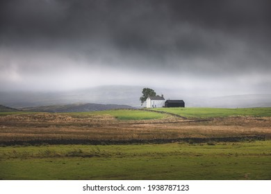 Lone, secluded farmhouse on a stormy, moody English countryside rural landscape in the North Pennines AONB, England UK.