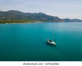 A lone ship in Thailand in the middle of the blue sea. Mountains with forests are stretching in the background. There are campsites along the shore.