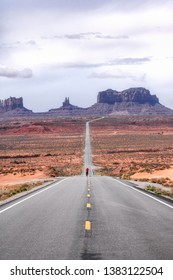 Lone silhouette of a person in a red coat on the road into Monument Valley. Forest Gump Viewpoint, Arizona.