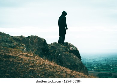 A lone sinister, hooded figure standing on a rocky outcrop looking out from top of a hill