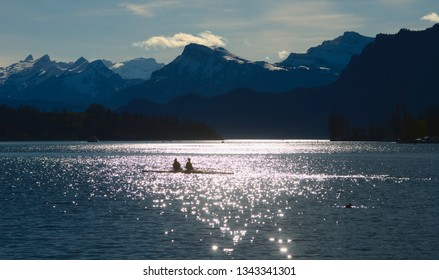A lone skiff against the light before mountain range