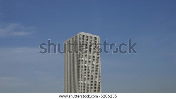 Lone skyscraper in the sky rising above the smog