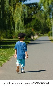 Lone small child in sporty street clothing and black hat walks away from camera in a park