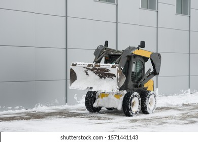 A lone snowplow minitractor is on a snow-cleared site. Copy space.
