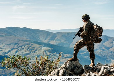 Lone soldier on a mountain in full equipment. soldier concept