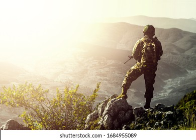 Lone soldier on a mountain in full equipment with faded sun flare. soldier concept