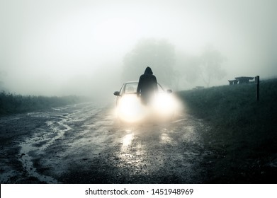 A lone, spooky, hooded figure standing in front of a car looking at an empty misty country road silhouetted at night by car headlights.
