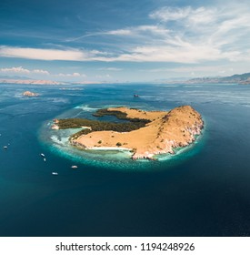 Lone standing island. Aerial drone shot. Komodo. Breathtaking panoramic view one of the amazing islands of the Komodo National Park surrounded by the Pacific ocean. Blue cloudy sky background.
