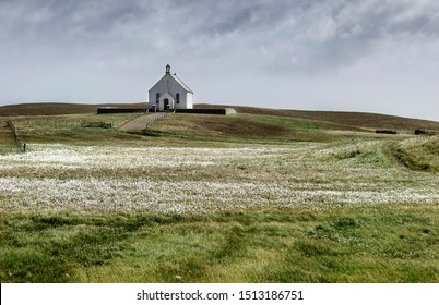 Lone Stonybreck village church, on Fair Isle island in Shetland with floral meadow and dramatic sky