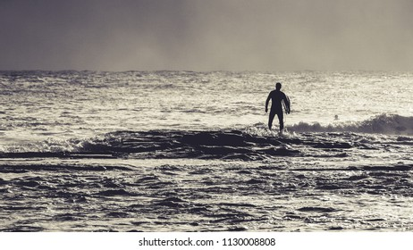A lone surfer heading out to sea in black and white