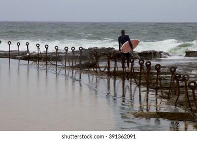 Lone surfer on path around Ocean Pool, Newcastle, NSW, Australia