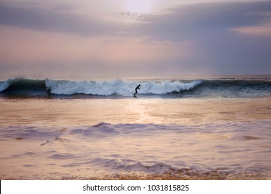 Lone surfer on surfboard, silhouetted against a crashing wave in Cornwall, Uk