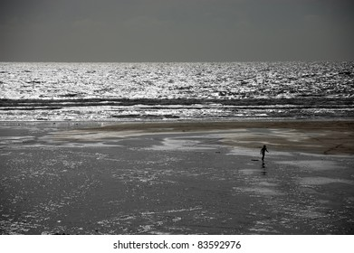 Lone surfer in silhouette walking on a beach with a bodyboard