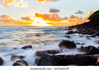Lone surfer silouhette standing on ocean rocks at sunrise with ocean cascading over rocks in the foreground