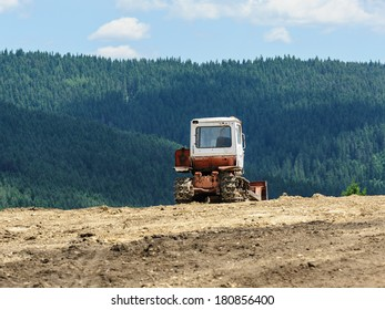 Lone tractor in mountain forest in background