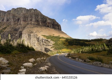 A lone white car makes a curve under the tall peaks of the Rocky Mountains