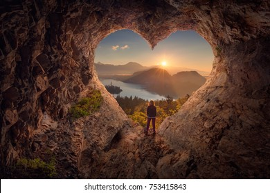 Lone woman enjoying in beautiful mountain nature, celebrating freedom and standing on edge of the cliff against the rising sun. Valentines day concept.