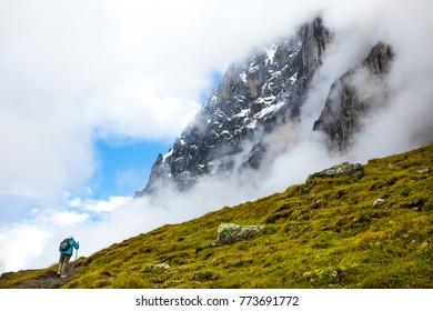 A lone woman hiker on the Eiger trail in the Alps mountains above Lauterbrunnen, Switzerland.