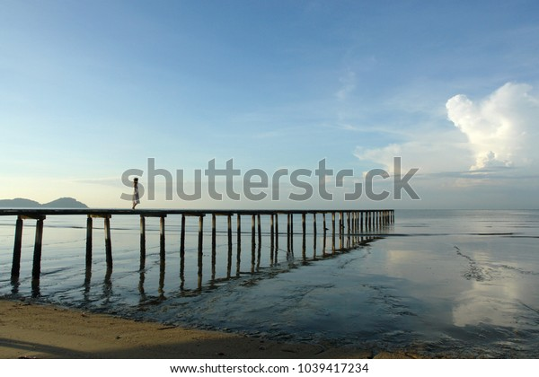 lone woman on a wooden boat pier with blue skies and sea