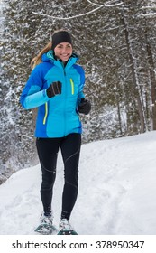 Lone woman running in the forest on snowshoes