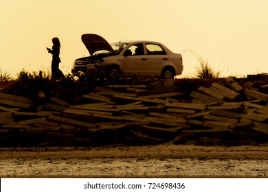 lone woman in silhouette with car trouble calling for help at roadside.