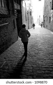 A lone woman is walking down a dark alley with two men in front of her in black and white.