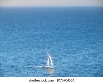 A lone yacht sails on the blue pacific ocean near Sydney Harbour, New South Wales, Australia