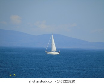 lone yacht sales up the Moray Firth  and stands out white against the blue of the sea, hills and sky