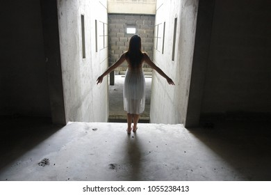 A lone young woman with her arms stretched standing on the edge of a ledge in ann abandoned building, contemplating on her future - feeling suicidal