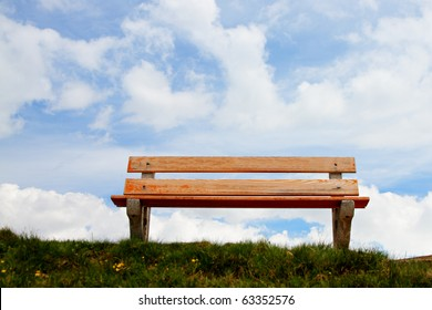 lone,empty wooden bench in front of a pretty blue sky, concept for a bench in heaven, a place to relax