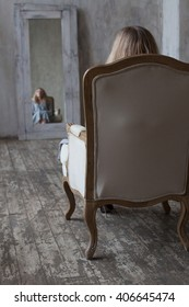 Loneliness. Alienation. Reflection. Mirror. Girl in an empty room sits back in a vintage chair, and looks at her reflection in the mirror.