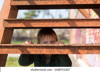 The loneliness of a child. A little boy looks out from behind the old metal steps.