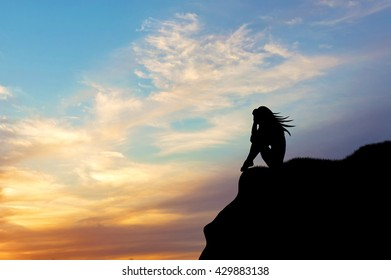 Loneliness concept. Silhouette of a woman alone on a hill at sunset