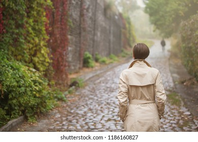 Loneliness concept. Woman in the street in autumn scenery